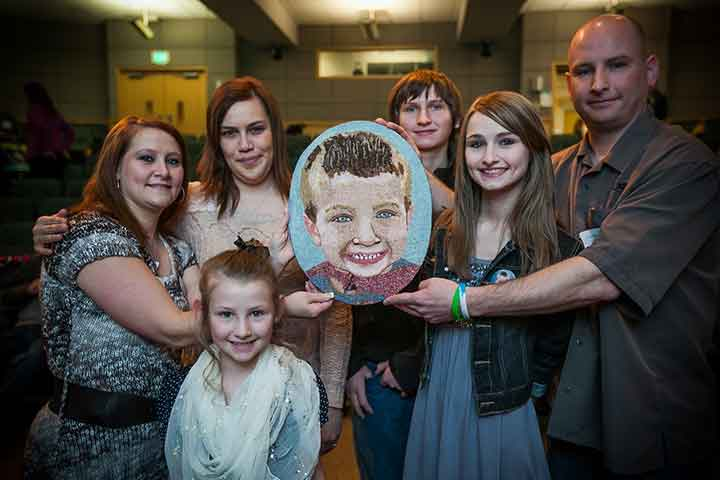 Family holding floragraph of loved one.